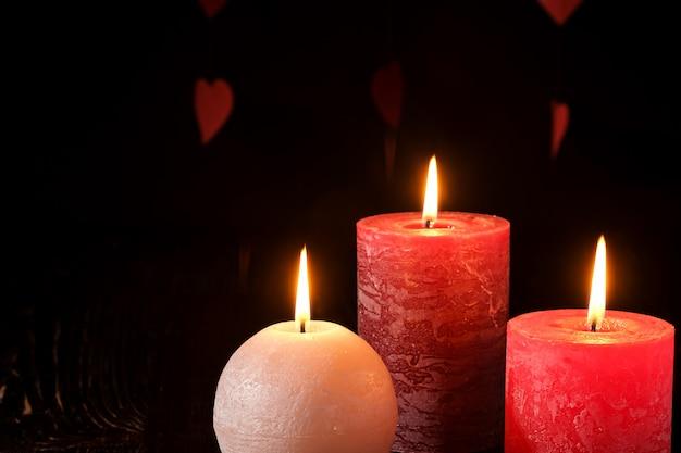 Três velas de chama de cera na luz romântica escura nos corações