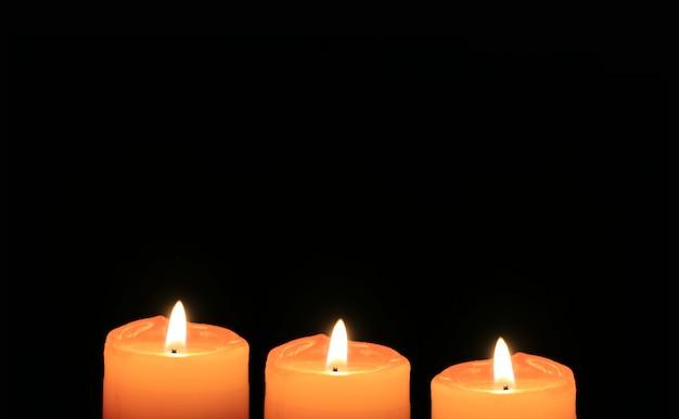 Três velas laranja brilhantes isoladas em fundo escuro