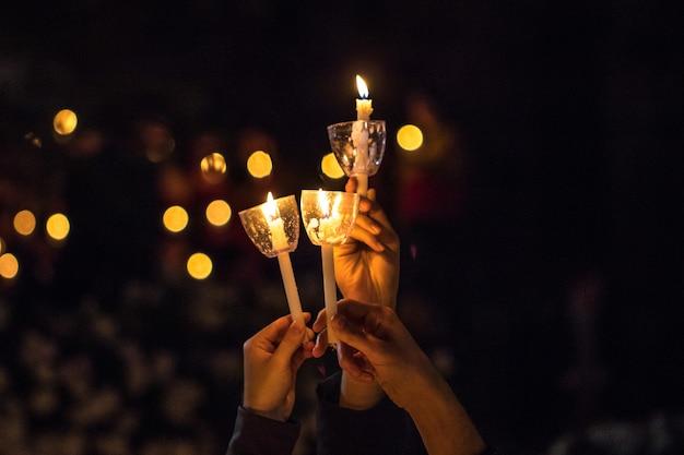Três velas nas mãos