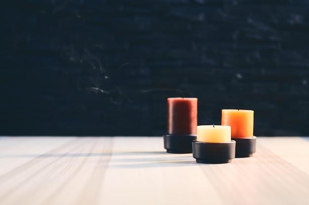 Três velas recém apagadas, fumando em uma mesa de madeira