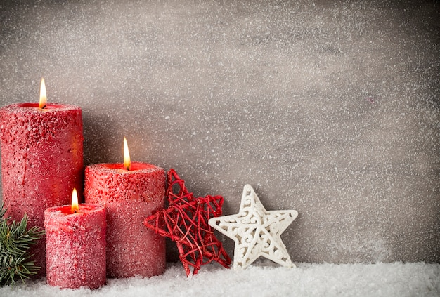 Três velas vermelhas na superfície cinza, decoração de natal. humor do advento.