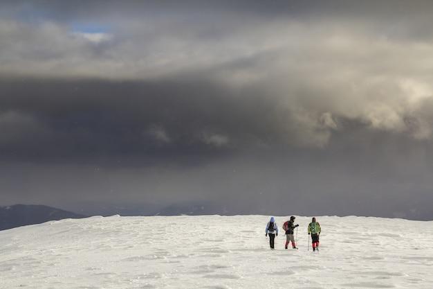 Três viajantes, caminhantes turistas com roupas brilhantes em um campo nevado