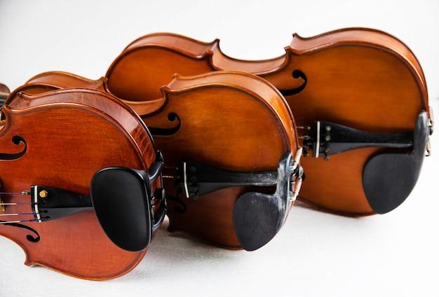 Três violinos empilhados no fundo branco.