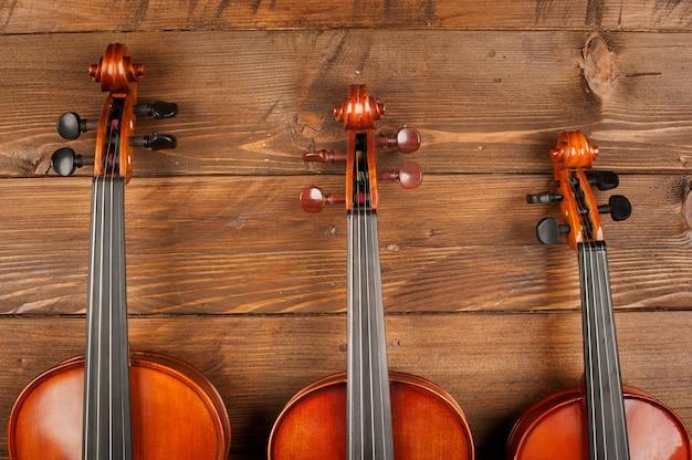 Três violinos na madeira