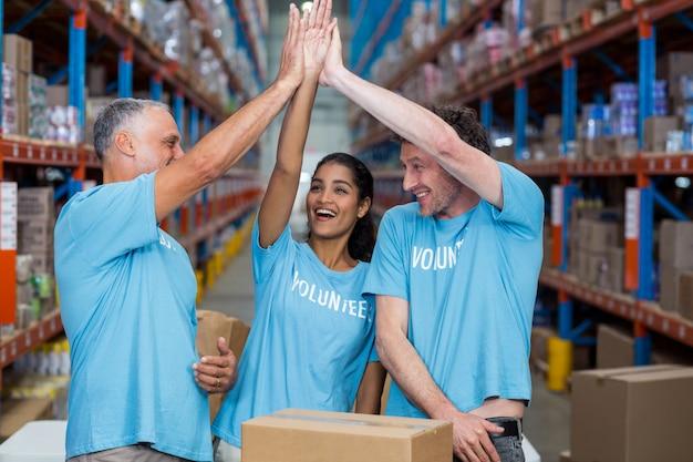 Três voluntários animados dando cinco