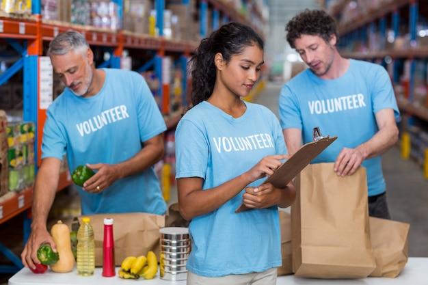 Três voluntários embalando comestíveis em caixa de papelão em um armazém
