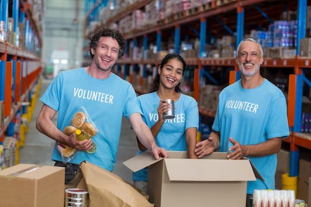 Três voluntários embalando comestíveis em caixa de papelão