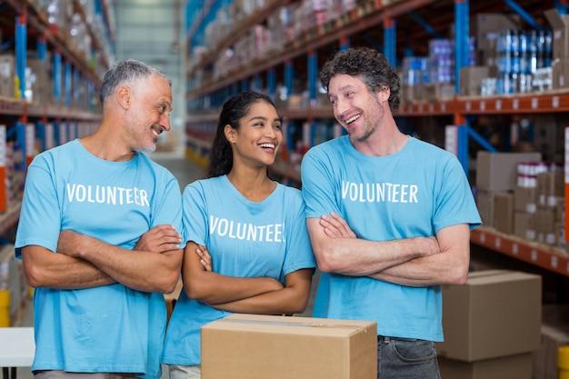 Três voluntários felizes em pé com os braços cruzados