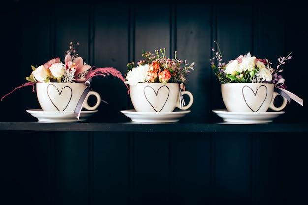Três xícaras brancas com flores na prateleira.