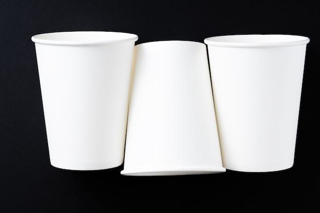 Três xícaras de café de papel branco em fundo preto. vista superior