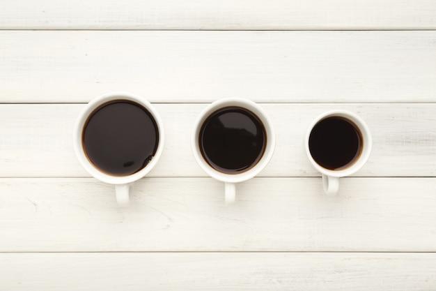 Três xícaras de café de tamanhos diferentes com café expresso preto forte. preparando bebidas em fundo branco de madeira, vista superior. conceito de energia e refresco, copie o espaço