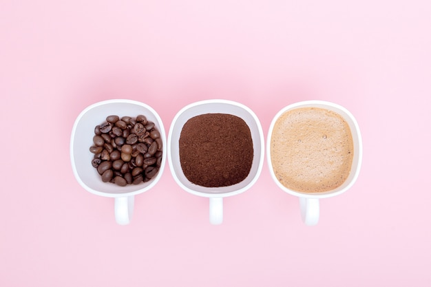 Três xícaras de diferentes estágios de preparação do café ou a fabricação da bebida do café isolada no fundo rosa, copie o espaço. vista do topo