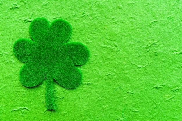 Trevo de papel verde sobre fundo de papel verde.