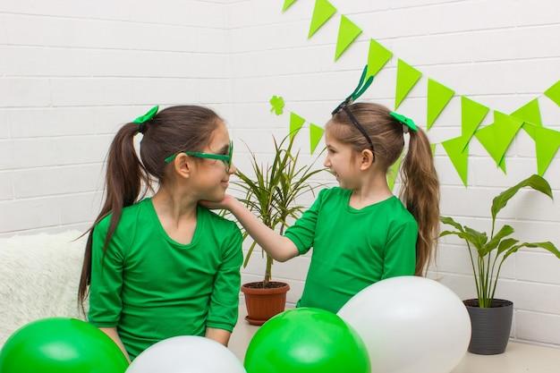 Trevo de trevo de duas garotas segurando balões se divertindo e comemorando o dia de são patrício