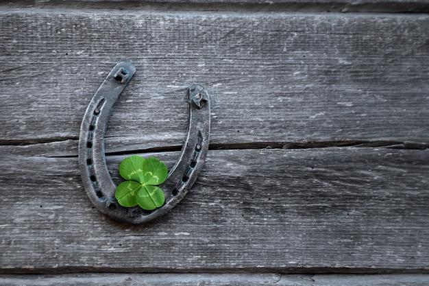 Trevo velho da ferradura e das quatro folhas em uma placa de madeira do vintage.