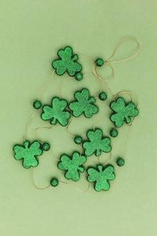 Trevos brilhantes sobre uma superfície verde para o dia de são patrício