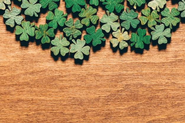 Trevos verdes de madeira que colocam no assoalho de madeira.