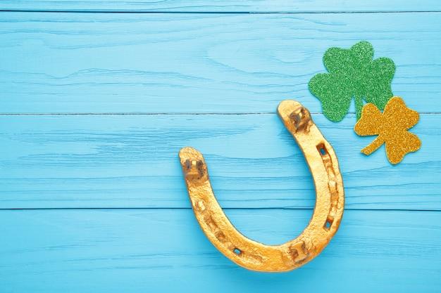 Trevos verdes e ferradura de ouro na parede de madeira azul para o feriado do dia de são patrício. vista do topo.