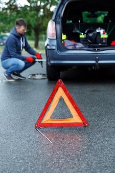 Triângulo de advertência na estrada e homem trocando a roda do carro