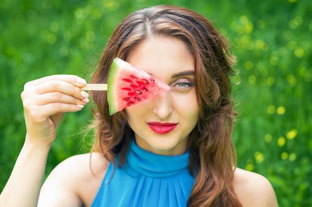 Triângulo de melancia no palito nas mãos no olho da menina, sobre um fundo verde.