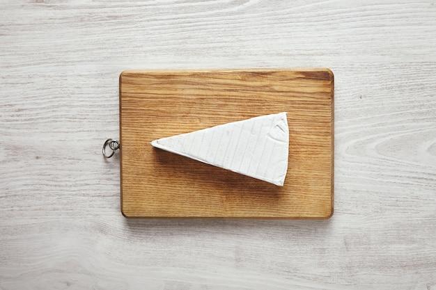 Triângulo fresco branco de saboroso queijo brie na tábua, isolado na mesa de madeira envelhecida branca no centro.