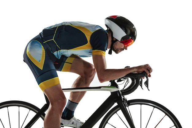 Triatlo atleta masculino ciclismo treinamento isolado no fundo branco do estúdio. triatleta apto caucasiano praticando no ciclismo, usando equipamentos esportivos. conceito de estilo de vida saudável, esporte, ação, movimento.