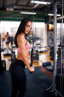 Tríceps apto do exercício da mulher que levanta peso no gym