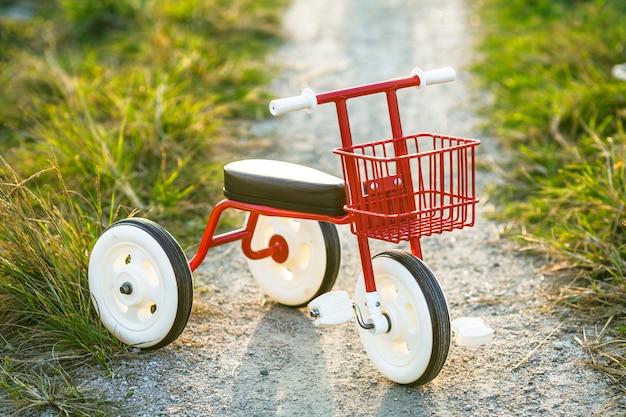 Triciclo bicicleta para crianças bicicleta azul e vermelho novo está na estrada no jardim para entreter crianças.