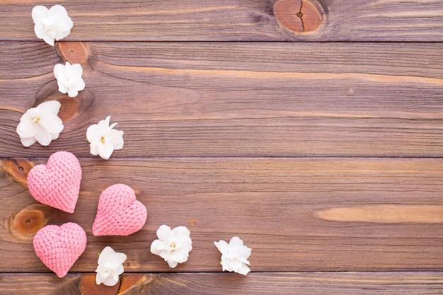 Tricô corações rosa e flores brancas em uma mesa de madeira.