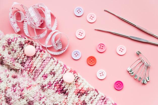 Tricô de crochê; fita métrica; botões; alfinetes de segurança e agulhas no pano de fundo rosa