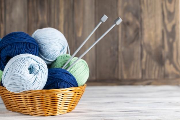 Tricô fio azul e verde em uma cesta com agulhas na madeira