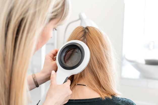Tricologista examina a condição do cabelo na cabeça do paciente com um dermatoscópio