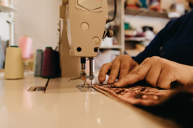 Tricotando um pedaço de tapete na máquina de costura