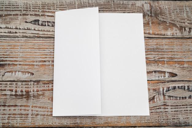 Trifold papel modelo branco na textura de madeira.