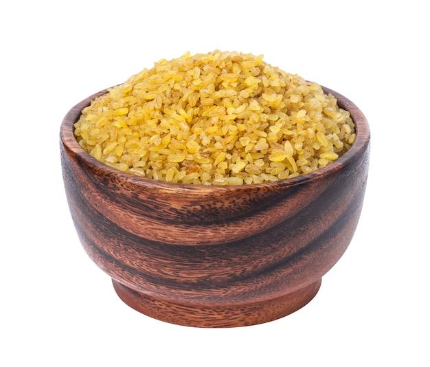 Trigo de bulgur seco na tigela de madeira isolado no branco