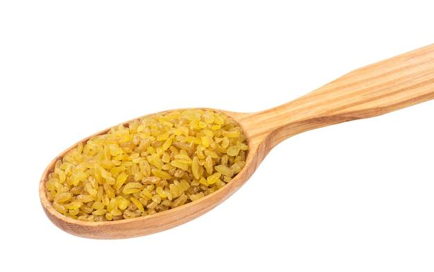 Trigo de trigo seco na colher de pau, isolado no branco