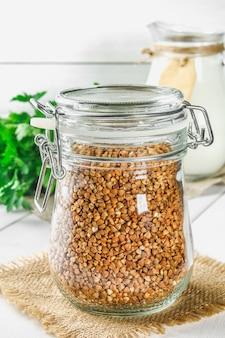 Trigo mourisco cru em um frasco de vidro no despedida em uma tabela de madeira no fundo da salsa.