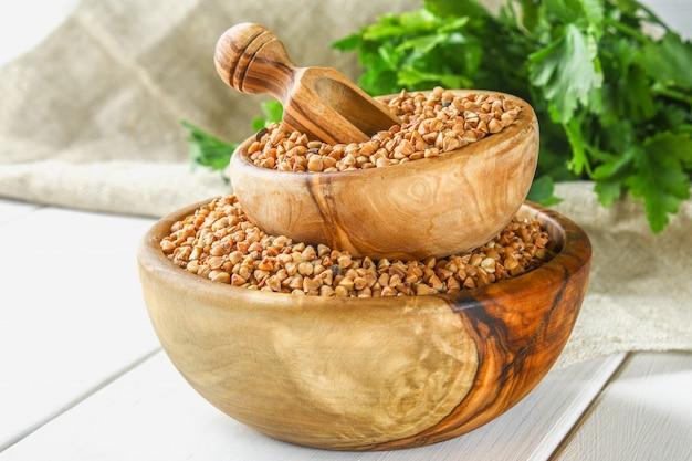 Trigo mourisco cru em umas bacias de madeira e uma colher no pano de saco em um fundo de madeira. comida de dieta saudável
