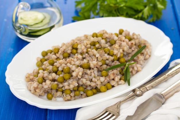 Trigo sarraceno com ervilhas no prato branco na superfície de madeira