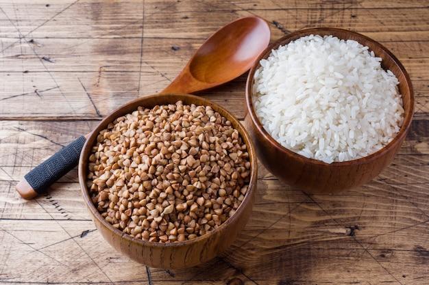 Trigo sarraceno e arroz cru em uma tigela de madeira