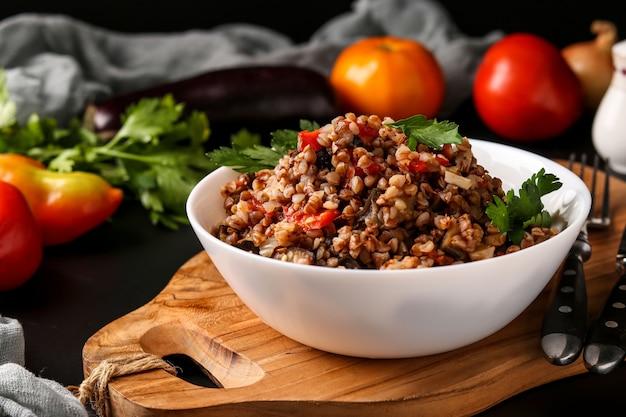 Trigo saudável cozido com legumes em uma tigela branca