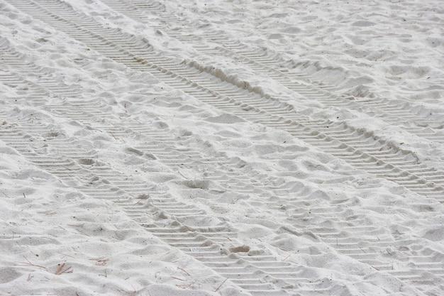 Trilha da roda do trator na praia branca pura da areia.