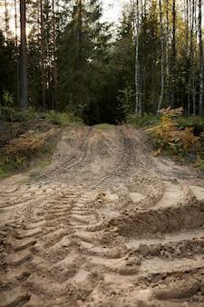 Trilha da roda em terreno arenoso de grande transporte, trator no canteiro de obras, estrada de areia. foto de alta qualidade