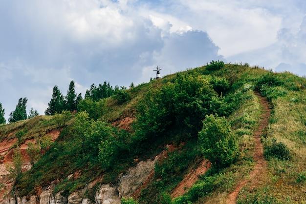 Trilha de caminhada na encosta da montanha em dia nublado de verão