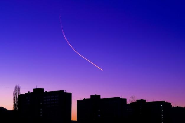 Trilha de condensação de avião sobre as silhuetas dos edifícios.
