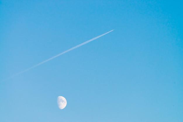 Trilha de condensação do jato acima da lua no céu azul claro do dia.