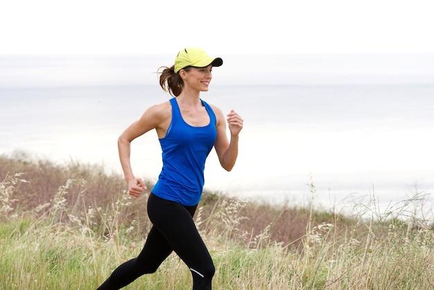 Trilha de mulher atlética correndo pelo mar no boné de beisebol