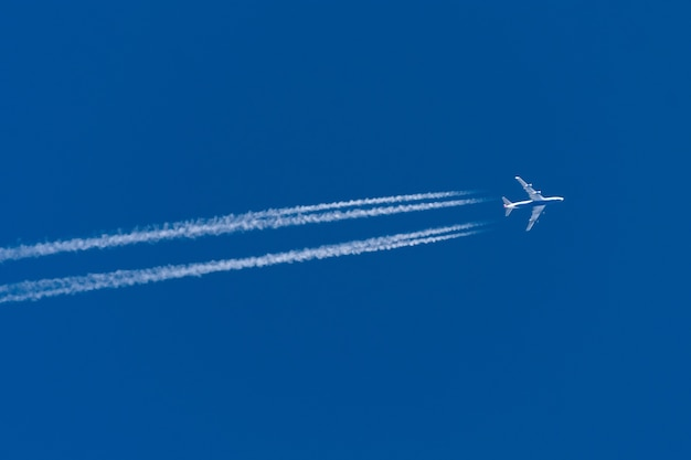Trilha do avião com quatro motores o céu azul.