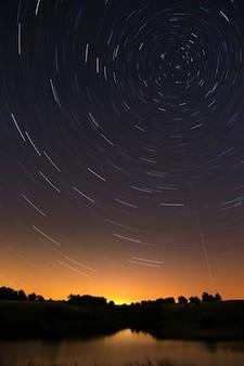 Trilha estelar no céu noturno com meteoros brilhantes e luzes de aeronaves.
