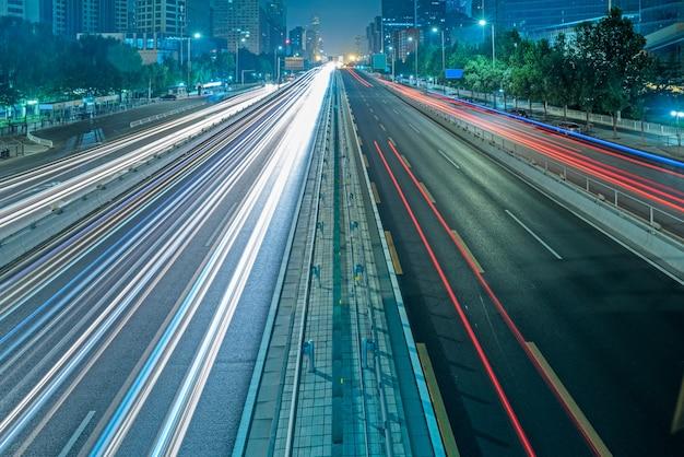 Trilhas borradas de trânsito na estrada à noite
